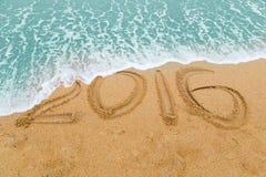 inscrição 2016 no Sandy Beach lavado fora com onda de aproximação Foto de Stock Royalty Free