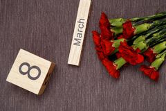 A inscrição o 8 de março com flores em um fundo cinzento Foto de Stock