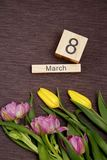 A inscrição o 8 de março com flores em um fundo cinzento Imagens de Stock