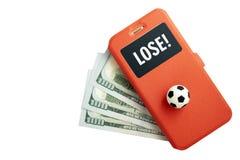 A inscrição PERDE na tela de um smartphone Uma bola do futebol e um telefone celular em uma mentira vermelha do caso em três cem  imagem de stock royalty free