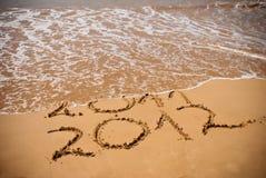 Inscripción 2011 y 2012 en una arena de la playa Foto de archivo