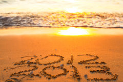Inscripción 2012 y 2013 en una arena de la playa Foto de archivo libre de regalías