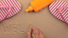 Inscripción AGRADABLE escrita a mano en la arena, entre los accesorios de la playa metrajes