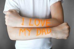 Inscripción anaranjada en las manos de un adolescente amo a mi papá fotos de archivo