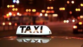 Inscripción brillante del taxi contra el paso de los coches en la calle de la noche almacen de metraje de vídeo