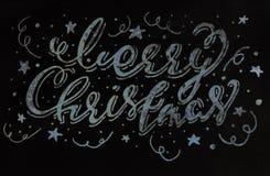 Inscripción caligráfica manuscrita de la Feliz Navidad en una textura gris de la pared textura y pintura de la pared Rastr Fotos de archivo