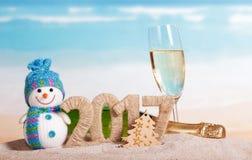 Inscripción 2017, champán de la Navidad, muñeco de nieve en la arena Foto de archivo libre de regalías