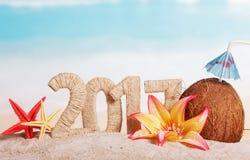 Inscripción 2017, coco, estrellas de mar y flores del Año Nuevo en el mar Foto de archivo libre de regalías
