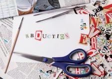 Inscripción de la abducción hecha con las letras cortadas Imágenes de archivo libres de regalías