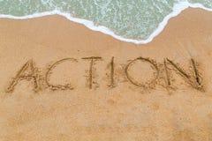 Inscripción de la ACCIÓN escrita en la playa arenosa con el acercamiento de la onda Fotografía de archivo libre de regalías