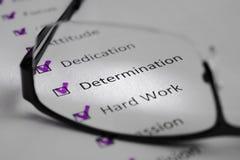 Inscripción de la DETERMINACIÓN en una hoja blanca Esto es una lista de control de motivación con los puntos para el éxito Enfren foto de archivo