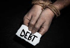Inscripción de la deuda en el papel en un hombre con las manos atadas con la cuerda en fondo negro fotografía de archivo libre de regalías