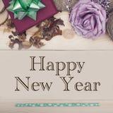 Inscripción de la Feliz Año Nuevo con las decoraciones de la Navidad en un fondo de madera ligero Fotografía de archivo