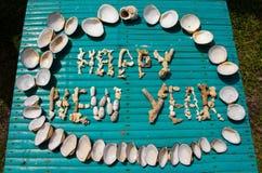 Inscripción de la Feliz Año Nuevo hecha por los corales en la tabla de madera Imagen de archivo