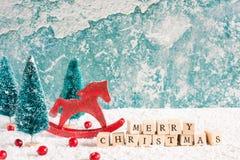 Inscripción de la Feliz Navidad con el caballo y abetos retros del juguete, bayas rojas y caja de regalo en la tabla de madera Imágenes de archivo libres de regalías