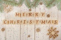 Inscripción de la Feliz Navidad en los cubos en el backgro de madera blanco Imágenes de archivo libres de regalías