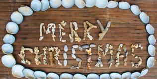 Inscripción de la Feliz Navidad hecha a mano con los corales del mar en fondo de madera Foto de archivo libre de regalías