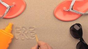 Inscripción de la LIBERTAD escrita a mano en la arena, entre los accesorios de la playa almacen de metraje de vídeo