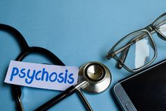 Inscripción de la psicosis con la vista del estetoscopio, de lentes y del smartphone en el fondo azul fotografía de archivo libre de regalías