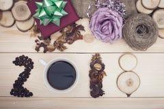 inscripción 2018 de los granos de café, de la taza, de flores secas y de rebanadas de madera con las decoraciones de la Navidad Fotos de archivo libres de regalías