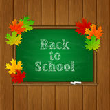 Inscripción de nuevo a escuela y hojas de arce en la pizarra verde Imagenes de archivo