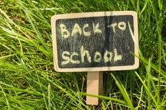 Inscripción de nuevo a la escuela escrita en tiza en un fondo de la pizarra de la hierba verde Imagen de archivo