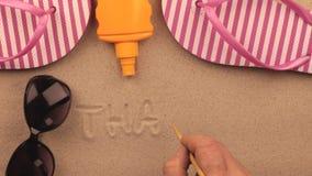 Inscripción de Tailandia escrita a mano en la arena, entre los accesorios de la playa almacen de metraje de vídeo