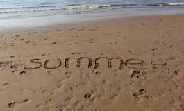 Inscripción del 'verano ', de las huellas en la arena y de las ondas del mar en la puesta del sol fotografía de archivo libre de regalías