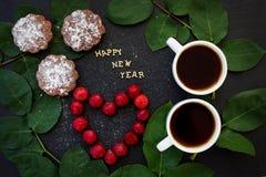Inscripción del Año Nuevo en un tablero negro con la magdalena Imagenes de archivo
