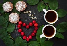 Inscripción del Año Nuevo en un tablero negro con la magdalena Imagen de archivo