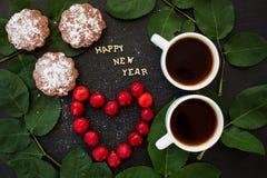 Inscripción del Año Nuevo en un tablero negro con la magdalena y el corazón en las cerezas de la forma Fotos de archivo