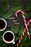 Inscripción del Año Nuevo en un tablero negro con las hojas de las puntillas y el caramelo rojo Imagen de archivo libre de regalías