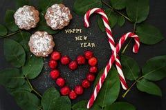Inscripción del Año Nuevo en un tablero negro con las magdalenas y el rojo del caramelo Foto de archivo