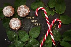 Inscripción del Año Nuevo en un tablero negro con las magdalenas y el rojo del caramelo Imagenes de archivo