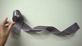 Inscripción del cáncer de cerebro, señora que pone la cinta gris en la tabla, campaña de concienciación almacen de video