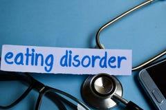 Inscripción del trastorno alimentario con la vista del estetoscopio, de lentes y del smartphone en el fondo azul imagenes de archivo