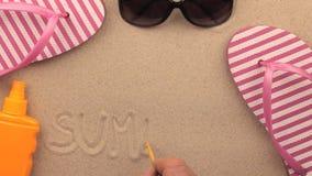 Inscripción del VERANO escrita a mano en la arena, entre los accesorios de la playa almacen de video
