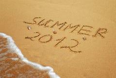 Inscripción en el verano mojado 2012 de la arena Imágenes de archivo libres de regalías