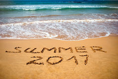 Inscripción en el verano mojado 2017 de la arena Foto del concepto de las vacaciones de verano en la playa tropical del océano de Imagen de archivo
