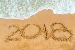 inscripción 2018 escrita en la playa arenosa con el acercamiento de la onda Foto de archivo