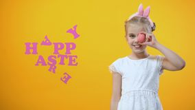 Inscripción feliz de Pascua, muchacha juguetona que sostiene el huevo coloreado delante de su ojo almacen de video