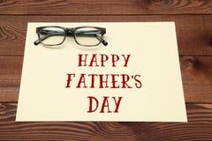 Inscripción feliz del día de padre con los vidrios en fondo de madera Fotos de archivo libres de regalías