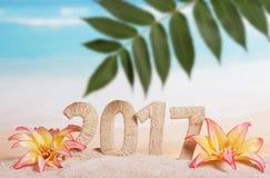 Inscripción 2017, hoja de palma y flores en arena contra el mar Fotos de archivo libres de regalías