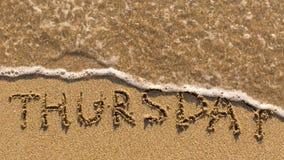 Inscripción JUEVES en una arena apacible de la playa con la onda suave Imagen de archivo