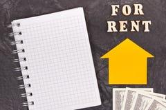 Inscripción para el alquiler, las monedas dólar y la libreta para las notas casa de alquiler o concepto plano imagen de archivo libre de regalías