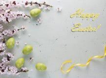 Inscripción Pascua feliz con la cinta amarilla brillante con las flores y los huevos de Pascua imagen de archivo libre de regalías
