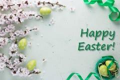 Inscripción Pascua feliz en el fondo ligero adornado con la cinta verde clara con las flores y los huevos de Pascua fotografía de archivo