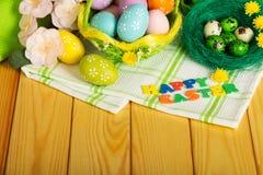 Inscripción PASCUA FELIZ, huevos de Pascua coloreados, flores, toalla fotos de archivo libres de regalías