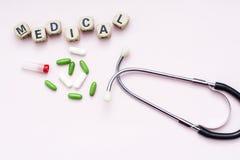 Inscripción rosada del fondo médica, píldoras y estetoscopio Fotografía de archivo