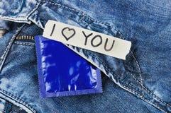 Inscripción TE AMO en el papel y el condón rasgados en paquete azul de la hoja en vaqueros Fotografía de archivo
